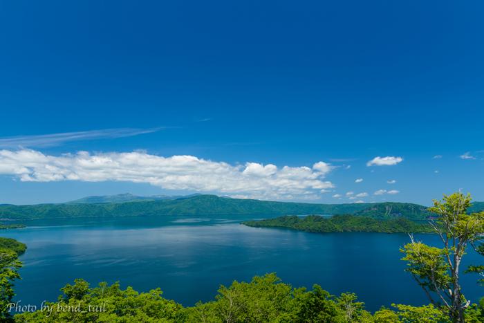 四季折々で美しい景色を見せてくれる十和田湖ですが、夏の美しさは格別です。静かな湖面が、陽射しを浴びてサファイヤのように輝き、抜けるような青空と白い雲のコントラストが美しさを引き立てています。