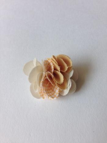 花びらのような形や丸くカットした布をランダムに重ねてボリュームを出すと、立体的に仕上がります。布は針と糸でしっかりと縫いとめましょう。