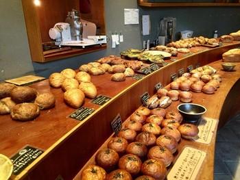 """緩やかにカーブしている木の陳列台は、フランスのチーズ台をモチーフに""""パンの美味しい魅力""""を最大限に引き出せる見せ方が出来るそう。"""