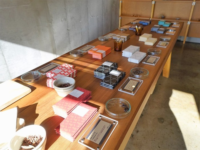 """店内に置かれた大きなテーブルの上には、カカオ70%×有機のサトウキビ30%の割合で作られたタブレットが並べられています。和柄のパッケージは、それぞれのチョコレートの味をイメージしていて、ジャケ買いならぬ""""パケ買い""""をする人も多いとか。全種類試食できるので「イメージだけでは選べない…」という人もご安心を。"""