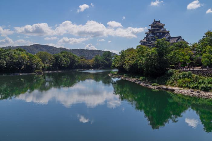 """「岡山」という地名は、旭川沿いにあった小高い丘""""岡山""""が、その名の起源。戦国時代の大名・宇喜多秀家が、領地拡大に伴って、1590年からこの丘(岡山)に城を築き、その後に形作られた城下町を含め「岡山」と呼ばれるようになりました。  岡山城は、烏城公園の北側の一角。天然の外堀として利用した旭川と豊かな緑、威風堂々たる城の眺めは、岡山ならではの景色です。"""