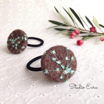 ココアブラウンの羊毛フエルトに、アヴリルの糸を巻きつけてアクセントに。キレイなミントグリーンの糸にちらりと見せるゴールドの糸が大人っぽい。特別なお出かけの日のワンポイントとしてもおすすめです。
