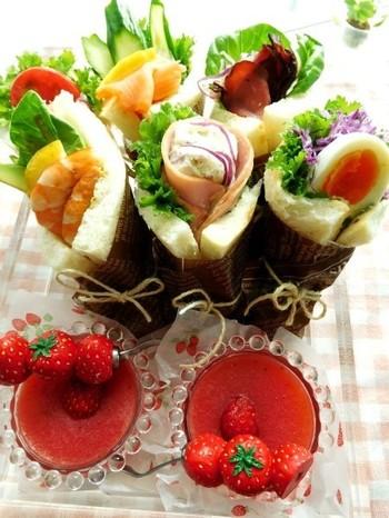 """簡単なのに、美しい!パンで具材を巻いただけ。サンドしないから""""サンドらず""""というそうです。ワックスペーパーなどでくるくると巻いて麻ひもで結び、深さのあるプラスチックカップなどに入れると、まるで花束のようできれいですね。"""