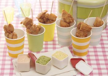 紙コップやプラスチックカップにおかずを入れるのもおすすめ。こちらは、食べやすいようにから揚げを串に刺して、可愛い紙コップに入れた、行楽弁当にピッタリの盛り付けです。3種のディップを好みでつけて食べます。