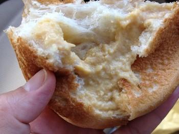 こちらが、噂の濃厚クリームが入ったクリームパンの中身。黄色というよりオレンジ色に近い色に驚き!濃厚なのは食べなくてもわかります。