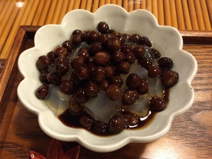 人気の秘密は、千葉県千倉産の天草を煮出して作った自家製寒天と、特製の蜜。風味豊かな寒天は、ぷるんとした食感が抜群。沖縄波照間島産の黒糖から手づくりした黒蜜もさらりとした甘さが自慢です。黒蜜と自家製寒天のマリアージュは、堪らない美味しさです。【画像は、北海道産の赤えんどうがたっぷり入った「豆かん」。】