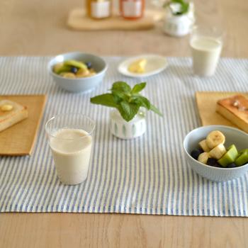 ブルーと白のストライプ柄のテーブルランナー。明るい木目調のテーブルとの色合いが爽やかなモーニングテーブルです。