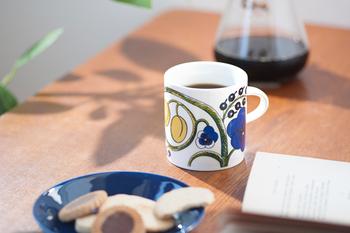 1969年に陶芸界の巨匠、ビルイエル・カイピアイネンがデザインし発表された【Paratiisi(パラティッシ)】。現在では「ARABIA(アラビア)社」を代表するシリーズです。  白い陶器に描かれるのはみずみずしい果実や草花。イエローとブルーのコントラストも華やかで、世界中で根強い人気があります。この写真の「カラー」の他にも白黒の「ブラック」、紫が美しい「パープル」も。
