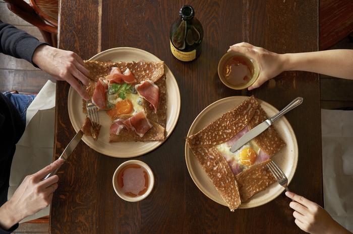 ガレット発祥の地、フランス・ブルターニュ地方では、ガレットをいただきながらシードル(発泡酒)を飲んでおしゃべりをするのが定番。そば粉のガレットの中には、卵やハム、きのこやベーコンなどの具が入り、仕上げに塗る塩入りのバターが香ばしいひと皿です。