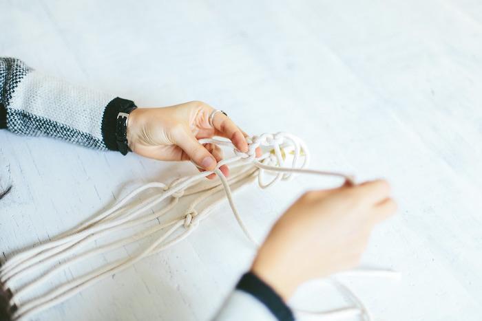 ロープを同じ長さにカットしてリングに通し(ない場合は省略)、紐の中央の部分でまとめて固結びしておきます。(※リングがない場合は、フックに掛けられるように、上部に空間を残しておきましょう。) 同じ長さのところで、2本ずつ固結びしていきます。