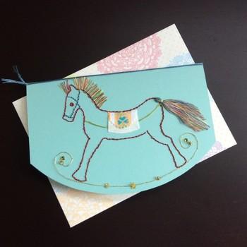 木馬のたてがみが、糸でフリンジになっています。 布のアップリケも効いていて、紙と布の異素材の組み合わせがおしゃれ。