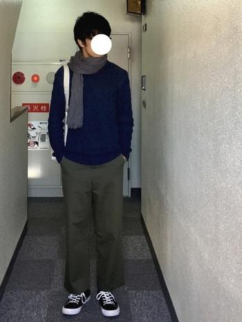 ネイビーのニットにカーキのワイドチノパンツを合わせた着こなしは、シンプルだけどちゃんとオシャレ!無造作に巻いたグレーのストールが、上下の色合いをしっかりとまとめています。