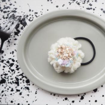 もこもこの毛糸で作ったお花のようなヘアゴムは、冬の装いにピッタリ。ベージュ、パープル、ピンクなど、淡いカラーが重なり合って表現されたお花の中心部が繊細。ナチュラルなお洋服とも相性◎です。