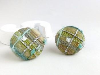 羊毛フェルトをベースにしたくるみボタンのイヤリングは。グリーン系のグラデーションで落ち着いた雰囲気。オフィスファッションにも使えそうです。