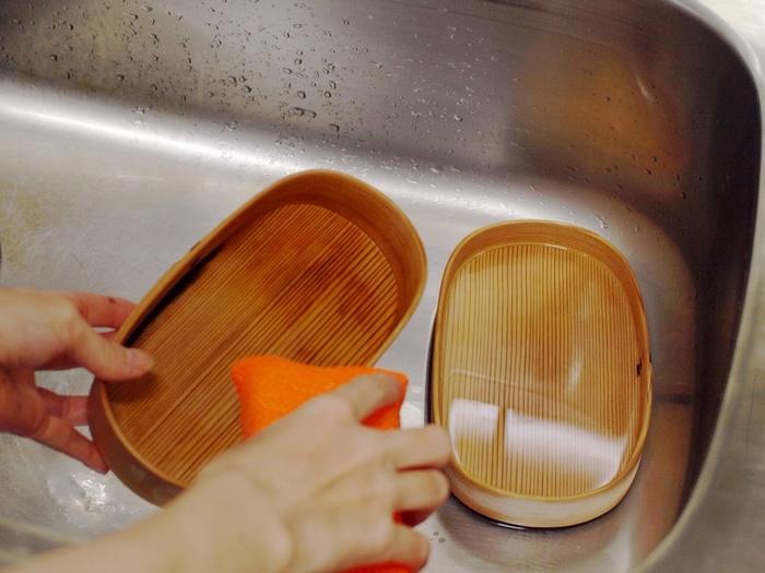 食べ終わった後はなるべく早く洗うようにしましょう。まずは、お湯、または水を注いで、汚れを軽く洗い落とします。  白木の無塗装の物は、しばらくぬるま湯に浸したあと、洗剤を使わず手かスポンジで優しくこすります。汚れがひどい時には、研磨剤の入ったクレンザーとたわしを使って、新しい木肌を出すように洗います。汚れが落ちたら、クレンザーが残らないように、しっかりすすぎ流してください。  漆塗り、ウレタン塗装のものは、中性洗剤を使っても大丈夫です。洗った後は、乾いた布で水分を拭き取りましょう。