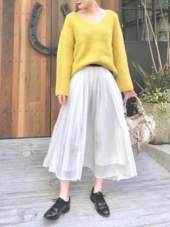 鮮やかなイエローのニットを主役にしたコーデ。ざっくりと深めのVネックが女性らしく、首周りもすっきり。ニットのカラーを引き立たせる白のプリーツスカートが、コーデに軽やかさをプラスしてくれます。こんなに明るいカラーのニットなら気持ちまでウキウキしてきそう♪