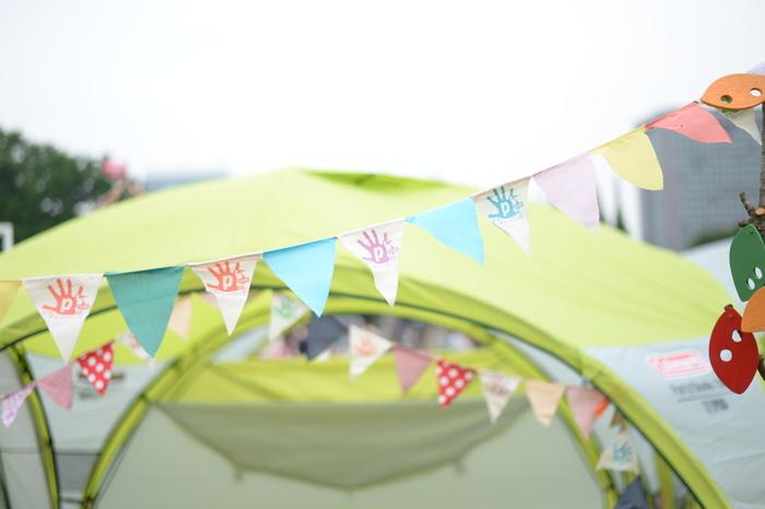 キャンプデコの定番・フラッグガーランドは、明るい色でテンションアップ! テントの場所を見失うことのない目印です。