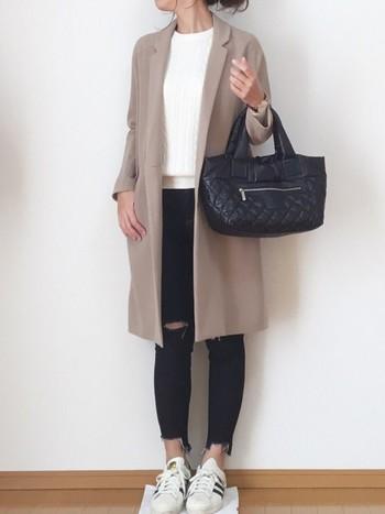 かっちりめのコート、バッグにあえてダメージジーンズを合わせてカジュアルダウン。インナーに仕込んだケーブルニットが、大人っぽい印象を与えてくれます。