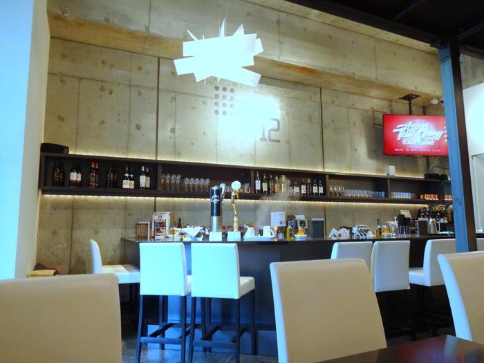 打ちっぱなしのコンクリート壁のスタイリッシュな店内。昼のカフェタイムと夜のバータイム、全く違う二つの顔を持つカフェ。