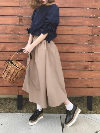 濃紺ブラウスにベージュのフレアスカートというシンプルコーデにも、かごバッグが大活躍!休日にぴったりの大人カジュアルスタイルです。
