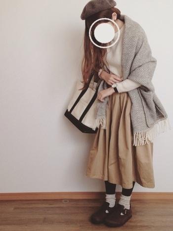 デートにもぴったりな、ベージュスカートとあたたかみあふれるショールを巻いた雰囲気のあるコーデです。ブラックタイツとソックスを重ねて、秋深まる季節でも◎