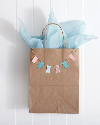 マスキングテープで作ったパステルのガーランドを紙袋に付けるだけです。不織布を中に入れて、おめかしすれば、さらにキュートな印象になりますよ。