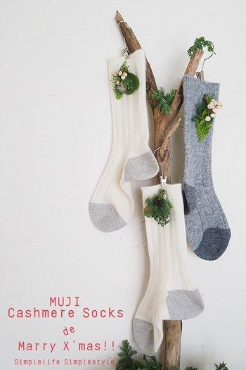 シンプルな靴下が簡単アレンジでクリスマス仕様に!作り方は靴下にワイヤーを通し、コサージュを留めて流木に吊るすだけ。選ぶ靴下のカラーによって雰囲気の違いを楽しんでみて。
