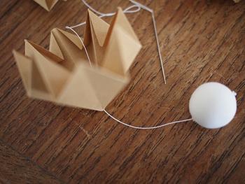 組み合わせる前に、紙粘土で作ったボールを針と糸で取り付けるのがポイント。真っ白のボールを付けることで、冬っぽさも演出できます。
