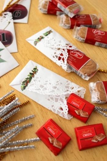 袋状に折ったレースペーパーの中に、キャンディーやチョコを入れて、モールのタイでツリーに飾り付けます。