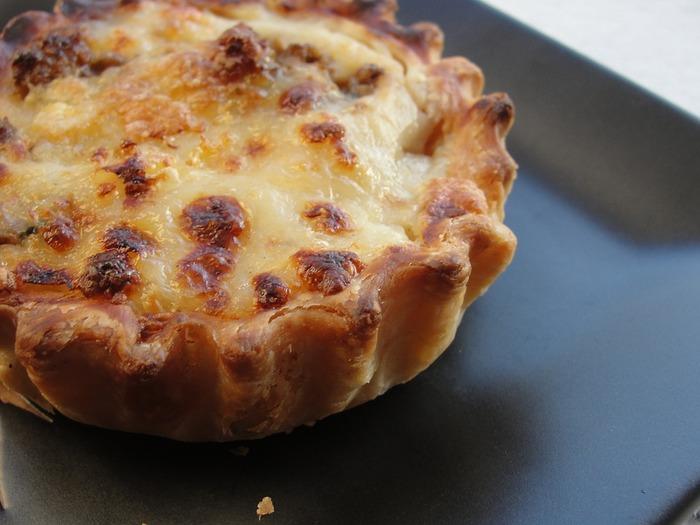 【材料】(4〜6人分) パフペイストリー500g、お好きなチーズ500g、卵3個、クリームチーズ200g、ねぎ1本、ベーコン100g、黒こしょう少々、パプリカパウダー少々、ナツメグ少々、ローズマリー少々、パセリ1/2束  【作り方】 1.チーズは粉状に、ねぎ、パセリはみじん切り、ベーコンは一口大にカットする 2.オーブンを200℃に予熱 3.パフペイストリーを、ベイキングトレイから少しはみ出すくらいの大きさにのばす 4.ベイキングトレイにのせたら、はみ出したふちを折り込む 5.生地全体にフォークで穴を開ける 6.残りの材料を全てまぜ合わせたらパフペイストリーにまんべんなくのせる 7.オーブンで30〜40分焼いて完成  ※画像はイメージです。
