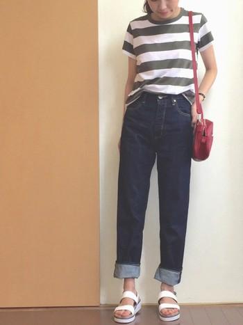 Tシャツ、ハイウエストデニム、白いサンダルといった定番スタイルも、太めのグレーボーダーで一気にオシャレに。赤いミニバッグがコーデのスパイスになります。