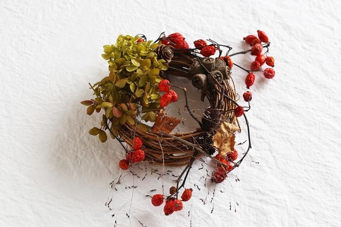 ●赤い実でクリスマス気分を演出 キャンドルの灯のように温かな印象のリースは、ディスプレイコーナーや室内のコート掛けなどに飾ってもいいですね。