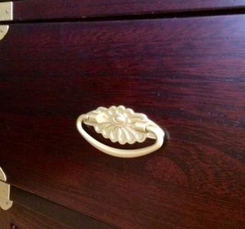 和風の現代家具にも・・・プレス加工された引き手金具にも、伝統的な菊の花の文様が用いられています。