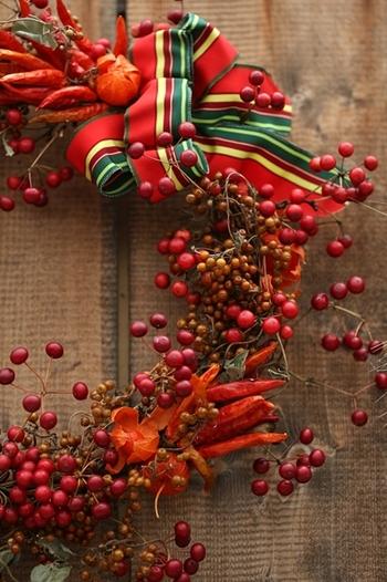 ●身近な食材で作る素朴なリース 赤い実をベースに唐辛子をアクセントとして使ったリースは、鮮やかな色使いでありながら素朴な雰囲気が漂います。実のつき方などを生かして抜け感のあるまとめかたをすると、重たい印象になりにくいですよ。