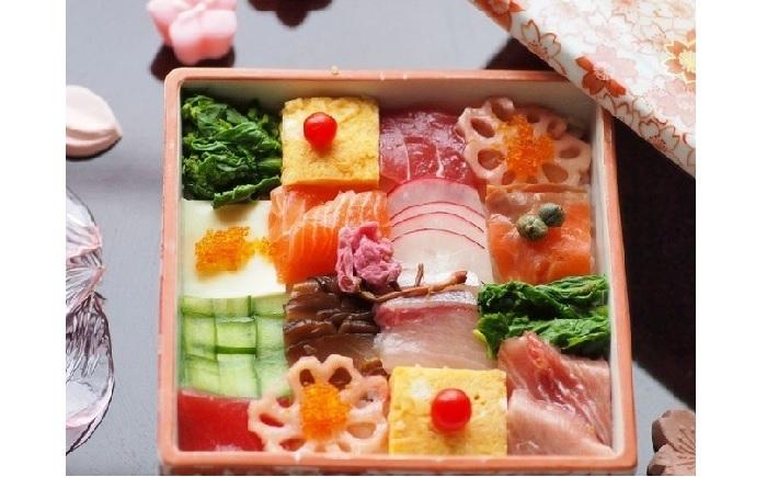 マグロ、はまち、ホタテにスモークサーモン、チーズ、きゅうり、椎茸、卵焼き、菜の花、レンコン、ラディッシュ。 陶の重箱に、色とりどりの宝物がギッシリ。編み込んだきゅうりの作り方は後述。