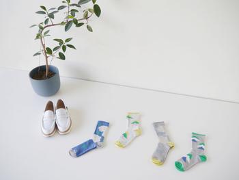 """重なった三角の柄がリズミカルな印象の靴下は""""yamabiko""""。ふわふわとしたお花柄が可愛らしい雰囲気の靴下は""""ohana""""。履くだけで気持ちがウキウキして、思わずお出かけしたくなりそう。"""