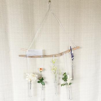 小瓶に紐をくくりつけたウォールハンギング。フックがあればスペースを選ばずお花を飾れます。