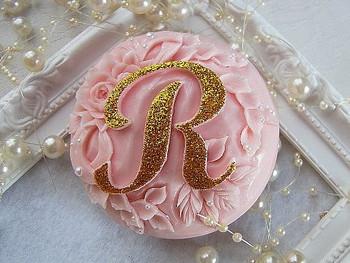 淡いピンクにゴールドのイニシャル入り。友人のイニシャルを入れたらプレゼントに喜ばれそう♪