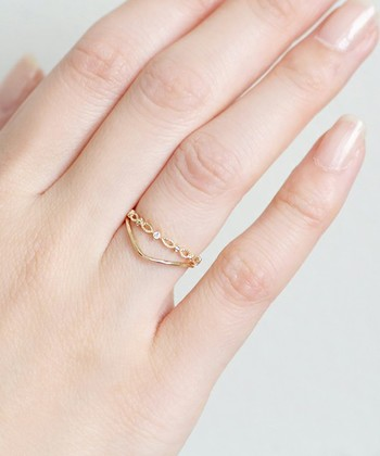 可愛らしいデザインとクールなデザインのタイプの異なるデザインの指輪を重ねて。 違うデザインの指輪でも細めのタイプなら合わせやすい。