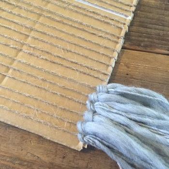 切込みが上下になるように向きを変え、カットした溝に縦方向に基本になる毛糸or麻紐を巻きつける。さらに、お好みの毛糸でフリンジを作る。