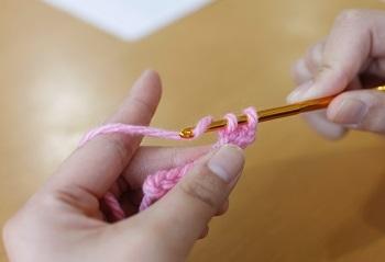 ④もう一度、かぎ針の先で糸をすくい取り、かぎ針にかかっている2本糸を引き抜きます。