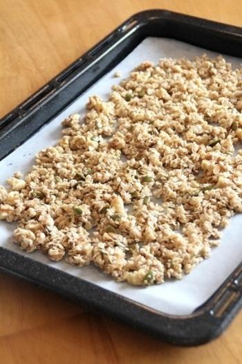 オーツ麦とナッツを混ぜたら、ごま油や水、砂糖、メープルシロップなどと絡めてオーブンで20~25分加熱します。10分ほどしたら一度取り出し、全体を軽く混ぜてから再度加熱。途中で何度か全体を混ぜることで噛み応えのある食感になります。