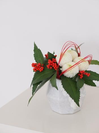 ブルーミングヴィルのマーブルポットに菊と千両を生けたお正月らしいアレンジメント。紅い水引をかけることで、よりお正月らしさが高まりますね。