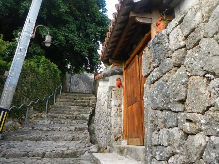沖縄ならではの石畳と石垣が、琉球文化の時の流れを感じさせてくれます。石垣の向こうには魔よけのシーサーを飾った赤レンガの民家が立ち並び、脇道に入ると樹齢200年以上の「アカギ」の大木にも出会えるそうです。