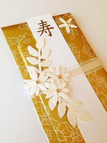 白いお花が立体的にアレンジされています。金色の光沢のある紙を使っているので、バッグから取り出しただけで注目を集めそう!