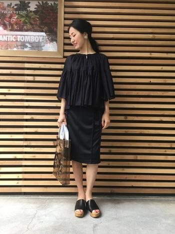 フォークロア感のあるギャザーたっぷりのブラウスにシンプルなスカートと、モノトーンでまとめたコーディネート。厚底のイタリアンレザーの黒のサンダルが効いたシックで上品な大人のボヘミアンスタイルです。