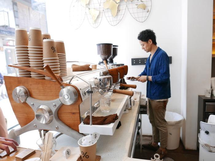 """「%Arabica」の""""スローガンは「See the world through coffee」""""。 店内には、世界最高峰のエスプレッソマシンが置かれ、クールで温かな雰囲気。人種や文化を超えてコーヒーを楽しめる空間です。海外からのバリスタが宿泊できる施設を併設する「%Arabica」では、若い外国人バリスタたちも店に立ちます。"""