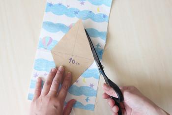 型紙を作ります。作りたいガーランドの形を2つつなげた形にするのがポイントです。 形は三角形でも、四角や円形でもお好みでOK! 型紙ができたら布をカットして、布をアイロンで半分に折ります。