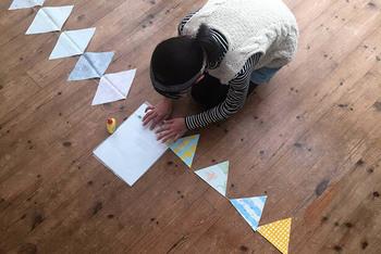 麻紐の上に布を広げ、並べます。折り目の部分で麻紐を挟むようにして、ボンドで留めていきます。これならミシンがなくても、子供といっしょに簡単に作れちゃいますね!
