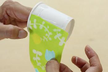 紙コップに、ボンドで布を貼り付けます。紙コップを1つハサミで切り開いて型紙を作っておくと、布の準備がしやすいですよ。
